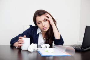 Sick woman at work drinking coffee