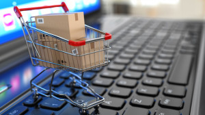 E-commerce. Shopping cart with cardboard boxes on laptop. 3d