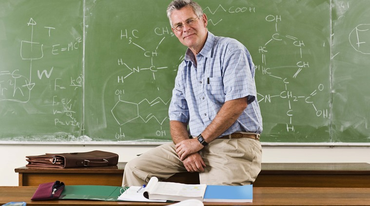Portrait of teacher sitting on desk in front of chalkboard