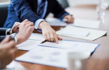 iStock-business-meeting-executive-papers-documents-pointing-515964910