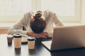 sleepy-office-worker-at-desk-with-multiple-coffees