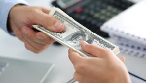 Man taking batch of hundred dollar bills