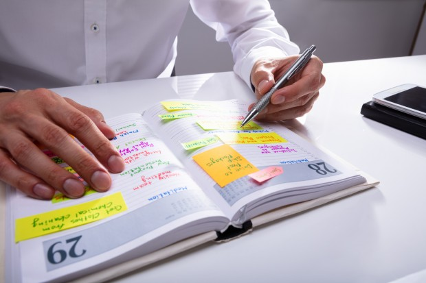 Businessman Writing Schedule In Diary